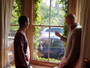 Two people inspecting a window during a home assessment