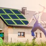 Happy builder jumps for joy in front of a house with solar panels, wind turbine and rolls of insulation, while holding a document