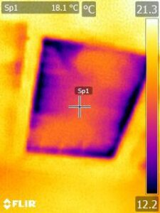A thermal camera image of heat loss around a loft hatch – orange/yellow areas are warm while blue/purple indicates cold spots, in this case showing draughts around the edges